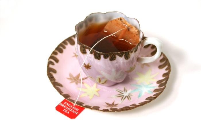 Antique cup with tea bag.